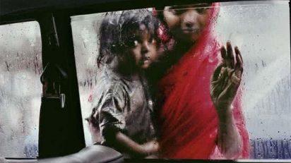 Madre_e_hijo_pidiendo_limosna_a_travs_de_la_ventana_de_un_taxi_durante_el_monzn_Steve_McCurry