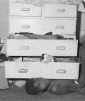 Roger Ballen. Outland. Unpublished child under chest of drawers. 2000.