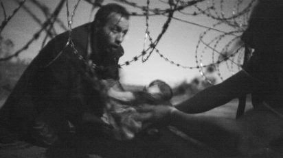 A man passes a baby through the fence at the Hungarian-Serbian border in Röszke, Hungary, 28 August 2015. © Warren Richardson, Australia.