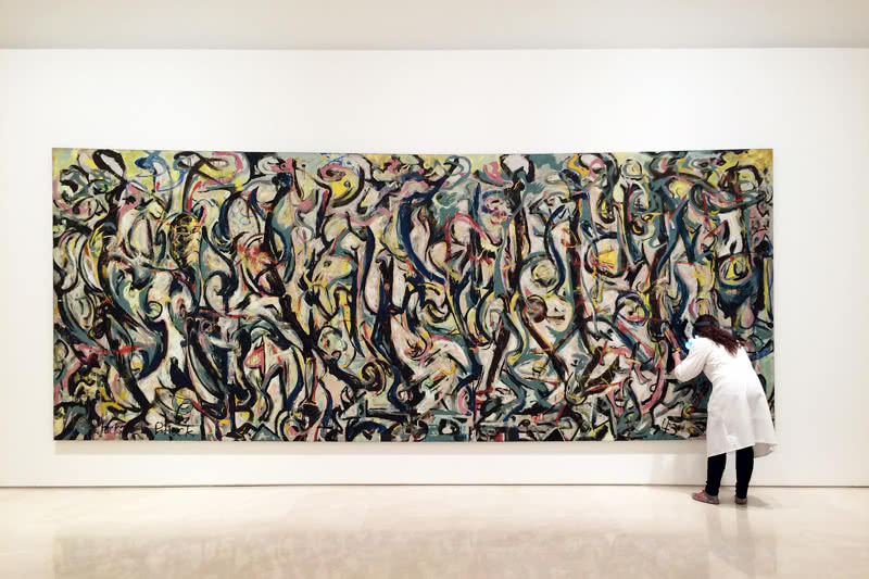 Una restauradora del Museo Picasso Málaga examina 'Mural' de Jackson Pollock a su llegada a la pinacoteca malagueña en donde se expone hasta el mes de septiembre © Museo Picasso Málaga.