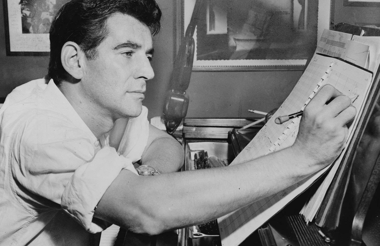 1955. Leonard Bernstein sentado al piano, anotando una partitura. Foto: Al Ravenna.