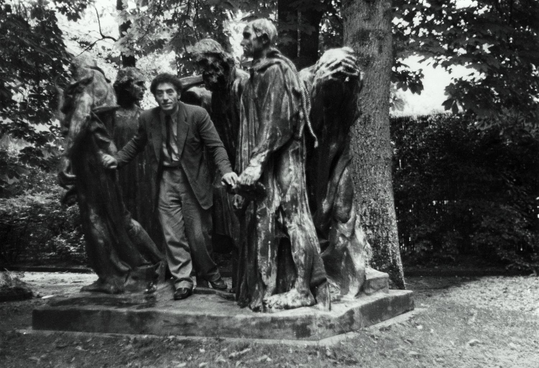 Patricia Matisse. Alberto Giacometti en el parque Eugène Rudier de Vésinet posando entre 'Los Burgueses de Calais', de Auguste Rodin, 1950. Archivos Fondation Giacometti, París.
